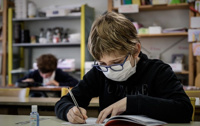 A pupil wearing a facemask attends a class at the private school Institut Sainte Genevieve in Paris on May 12, 2020, as the schools in France gradually reopen a day after a partial lifting of restrictions due to the Covid-19 pandemic caused by the novel coronavirus came into effect. (Photo by PHILIPPE LOPEZ / AFP)