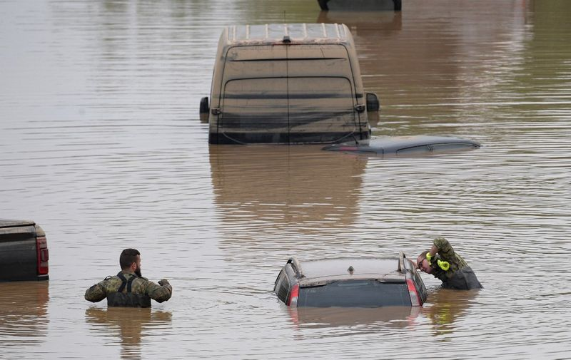 Soldiers of the German armed forces Bundeswehr search for flood victims in submerged vehicles on the federal highway B265 in Erftstadt, western Germany, on July 17, 2021, after heavy rains hit parts of the country, causing widespread flooding and major damage. - Rescue workers scrambled on July 17 to find survivors and victims of the devastation wreaked by the worst floods to hit western Europe in living memory, which have already left more than 150 people dead and dozens more missing. (Photo by SEBASTIEN BOZON / AFP)