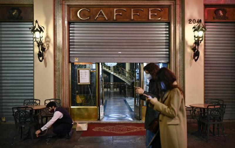 """Two women walk past the """"Caffe Torino"""" as a waiter prepares to close in downtown Turin, on October 26, 2020, as the country faces a second wave of infections to the Covid-19 (the novel coronavirus). - Italy's Prime Minister Giuseppe Conte tightened nationwide coronavirus restrictions on October 25, 2020 after the country registered a record number of new cases, despite opposition from regional heads and street protests over curfews. Cinemas, theatres, gyms and swimming pools must all close under the new rules, which come into force on October 26, 2020 and run until November 24, while restaurants and bars will stop serving at 6pm, the prime minister's office said. (Photo by Marco BERTORELLO / AFP)"""