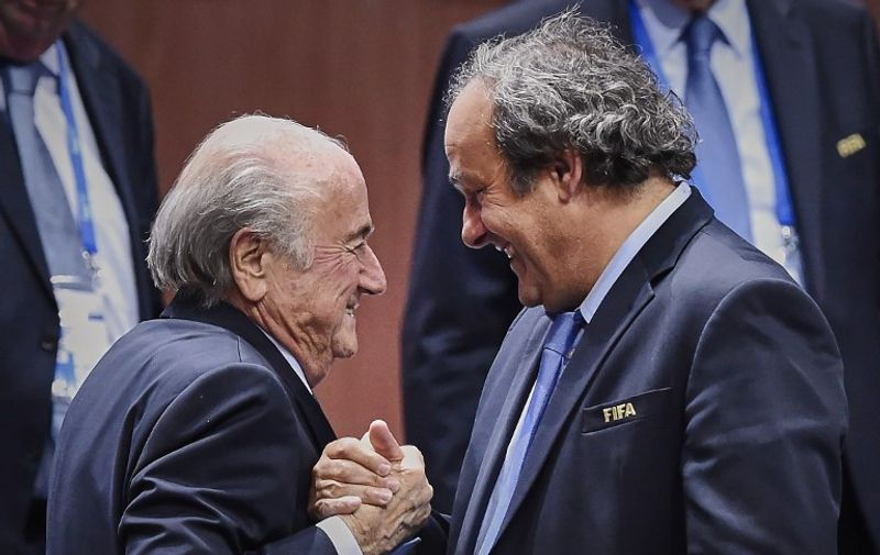 FIFA President Sepp Blatter (Foreground-L) shakes hands with UEFA president Michel Platini after being re-elected following a vote to decide on the FIFA presidency in Zurich on May 29, 2015. Sepp Blatter won the FIFA presidency for a fifth time after his challenger Prince Ali bin al Hussein withdrew just before a scheduled second round. AFP PHOTO / MICHAEL BUHOLZER / AFP / MICHAEL BUHOLZER