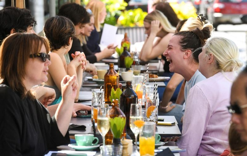 People enjoy a meal at a cafe in Melbourne on October 22, 2021, following the midnight lifting of coronavirus restrictions in one of the world's most locked-down cities. (Photo by William WEST / AFP)