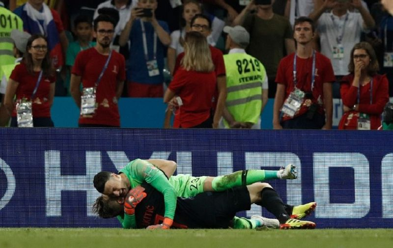 Croatia's midfielder Ivan Rakitic celebrates with Croatia's goalkeeper Danijel Subasic during the Russia 2018 World Cup quarter-final football match between Russia and Croatia at the Fisht Stadium in Sochi on July 7, 2018. Croatia beat Russia 4-3 on penalties on Saturday to set up a World Cup semi-final against England after a dramatic match full of twists and turns. / AFP PHOTO / Adrian DENNIS / RESTRICTED TO EDITORIAL USE - NO MOBILE PUSH ALERTS/DOWNLOADS