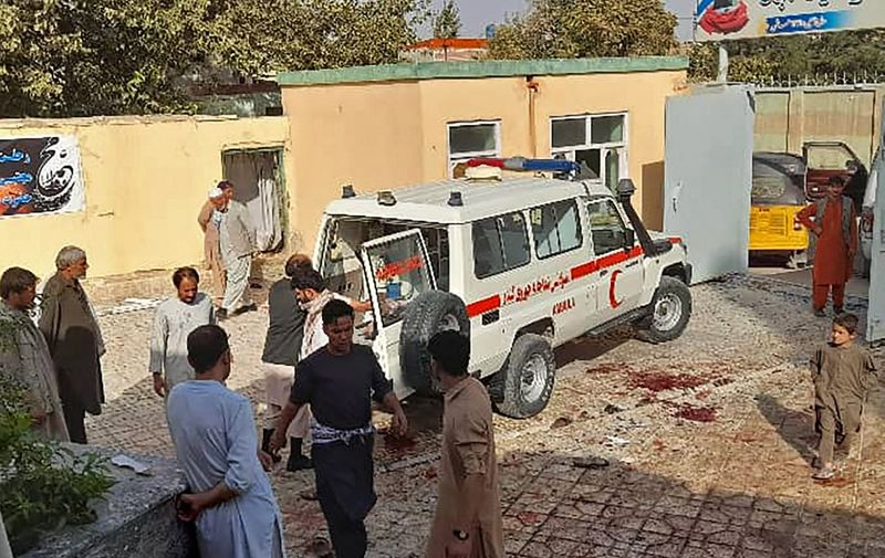 EDITORS NOTE: Graphic content / Afghan men stand next to an ambulance after a bomb attack at a mosque in Kunduz on October 8, 2021. (Photo by - / AFP)