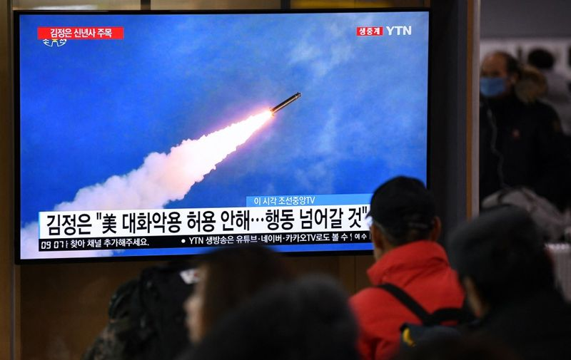 """People watch a television news programme showing file footage of North Korea's missile test, at a railway station in Seoul on January 1, 2020. - North Korean leader Kim Jong Un has declared an end to its moratoriums on nuclear and intercontinental ballistic missile tests and threatened a demonstration of a """"new strategic weapon"""" soon. (Photo by Jung Yeon-je / AFP)"""