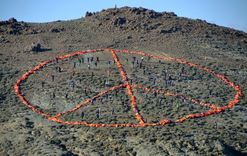 """A handout photo released by Greenpeace and taken on New Year's Day, January 1, 2016 on the Greek island of Lesbos shows members of a Doctors without Borders (MSF) and Greenpeace team together with groups such as Sea-Watch, the Dutch Refugee Boat Foundation and local communities standing within a peace sign created from over 3,000 discarded refugee life jackets, calling for safe passage to those fleeing war, poverty and oppression. More than one million migrants and refugees reached Europe in 2015, mainly fleeing violence in Afghanistan, Iraq and Syria, of whom four in five travelled via the Greek islands. / AFP / Greenpeace / FLORIAN SCHULZ / RESTRICTED TO EDITORIAL USE - MANDATORY CREDIT """"AFP PHOTO / FLORIAN SCHULZ / MSF / GREENPEACE """" - NO MARKETING NO ADVERTISING CAMPAIGNS - DISTRIBUTED AS A SERVICE TO CLIENTS - NO ARCHIVE"""