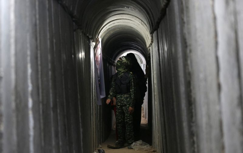 A Palestinian boy walks inside a tunnel used for military exercises during a weapon exhibition at a Hamas-run youth summer camp, in Gaza City, on July 21, 2016. (Photo by MOHAMMED ABED / AFP)