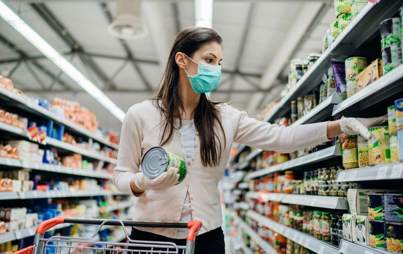 Woman preparing for pathogen virus pandemic spread quarantine.Choosing nonperishable food essentials.Budget buying at a supply store.Pandemic quarantine preparation.Emergency to buy list
