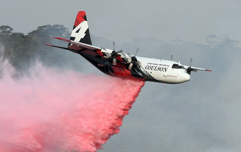 """(FILES) This file photo taken on January 10, 2020 shows a C-130 Hercules plane from the New South Wales Rural Fire Service dropping fire retardent to protect a property during an operation to douse bushfires in Penrose, in Australia's New South Wales state. - Three people died when a C-130 Hercules water-bombing plane crashed southwest of Sydney on January 23, 2020, setting off a """"large fireball"""", Australian officials said, as bushfires flared across the country's southeast. (Photo by SAEED KHAN / AFP)"""