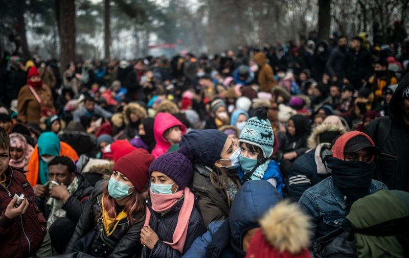 Migrants with protective masks wait at the buffer zone at Turkey-Greece border at Pazarkule, in Edirne district, on February 29, 2020. - Thousands of migrants stuck on the Turkey-Greece border clashed with Greek police on February 29, 2020, according to an AFP photographer at the scene. Greek police fired tear gas at migrants who have amassed at a border crossing in the western Turkish province of Edirne, some of whom responded by hurling stones at the officers. The clashes come as Greece bolsters its border after Ankara said it would no longer prevent refugees from crossing into Europe following the death of 33 Turkish troops in northern Syria. (Photo by BULENT KILIC / AFP)