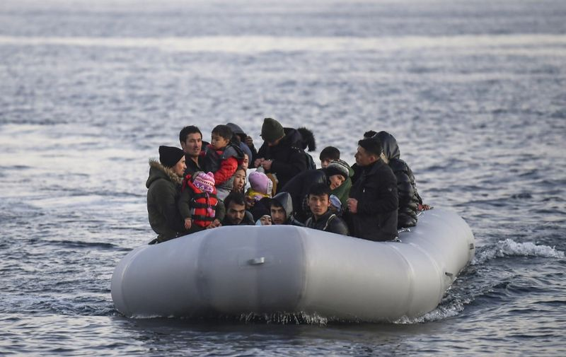 Refugees and migrants aboard an inflatable boat arrive in the Greek island of Lesbos on March 2, 2020. - Around 500 migrants landed on Sunday morning in around 10 vessels, according to an AFP tally, their crossing made easier by the good weather conditions. Another four vessels carrying 120 people landed on the neighbouring island of Chios, and two vessels carrying 80 migrants landed on Samos, further to the south, ANA reported. According to the Greek coastguard, around 180 migrants arrived Saturday on Lesbos and Samos, making the crossing from Turkey despite strong winds. (Photo by ARIS MESSINIS / AFP)