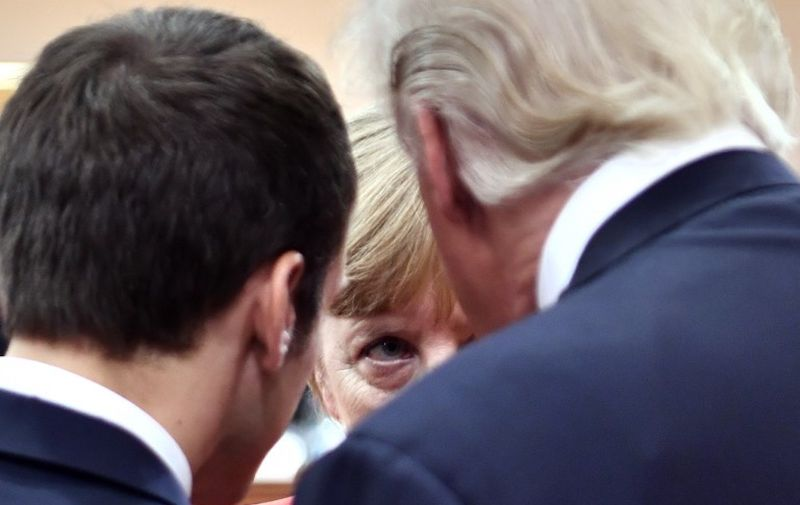 (L-R) French President Emmanuel Macron, German Chancellor Angela Merkel and US President Donald Trump confer at the start of the first working session of the G20 meeting in Hamburg, northern Germany, on July 7. - Leaders of the world's top economies will gather from July 7 to 8, 2017 in Germany for likely the stormiest G20 summit in years, with disagreements ranging from wars to climate change and global trade. (Photo by John MACDOUGALL / various sources / AFP)