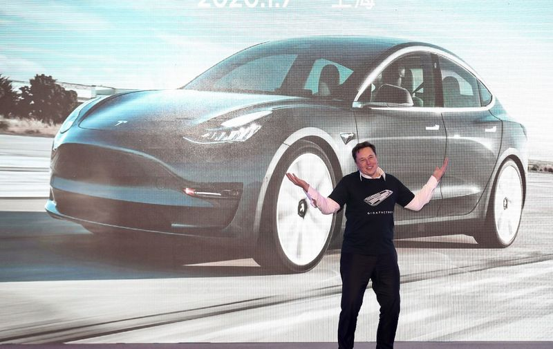 "Tesla CEO Elon Musk gestures during the Tesla China-made Model 3 Delivery Ceremony in Shanghai. - Tesla CEO Elon Musk presented the first batch of made-in-China cars to ordinary buyers on January 7, 2020 in a milestone for the company's new Shanghai ""giga-factory"", but which comes as sales decelerate in the world's largest electric-vehicle market. (Photo by STR / AFP) / China OUT"