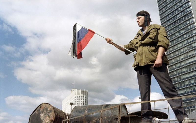 A man waves a russian flag during the funeral procession of victims of the coup in front of the Russian White House in Moscow on August 24, 1991, after the coup attemp failed. / AFP PHOTO / DIMITRI KOROTAYEV