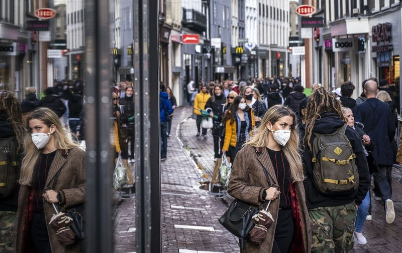 People wearing face masks walk on a shopping street in the center of Amsterdam on October 11, 2020. - The Dutch government is expected to take new measures to halt the spread the Covid-19 disease caused by the novel coronavirus. (Photo by Ramon van Flymen / ANP / AFP) / Netherlands OUT