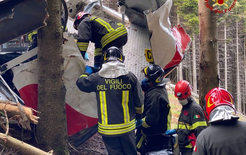 """A photo taken on May 23, 2021 and handout on May 24, 2021 by The Italian Firefighters """"Vigili del Fuoco"""" shows rescuers at work by a cable car that crashed to the ground in the resort town of Stresa on the shores of Lake Maggiore in the Piedmont region. - 14 people died on May 23 after a cable car crashed to the ground in northern Italy, emergency services said. (Photo by Handout / Vigili del Fuoco / AFP) / RESTRICTED TO EDITORIAL USE - MANDATORY CREDIT """"AFP PHOTO / VIGILI DEL FUOCO / HANDOUT """" - NO MARKETING - NO ADVERTISING CAMPAIGNS - DISTRIBUTED AS A SERVICE TO CLIENTS"""