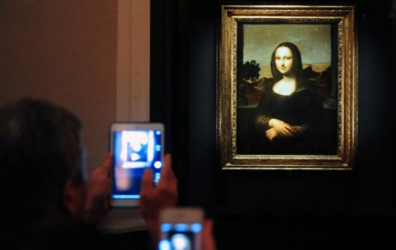"Members of the media take pictures during the media preview of The World Premiere of Leonardo Da Vinci's painting ""Earlier Mona Lisa"" exhibition in Singapore on December 15, 2014. The World Premiere of Leonardo Da Vinci's exhibition will begin on December 16 till February 1, 2015. AFP PHOTO / MOHD FYROL RESTRICTED TO EDITORIAL USE, MANDATORY MENTION OF THE ARTIST UPON PUBLICATION, TO ILLUSTRATE THE EVENT AS SPECIFIED IN THE CAPTION."