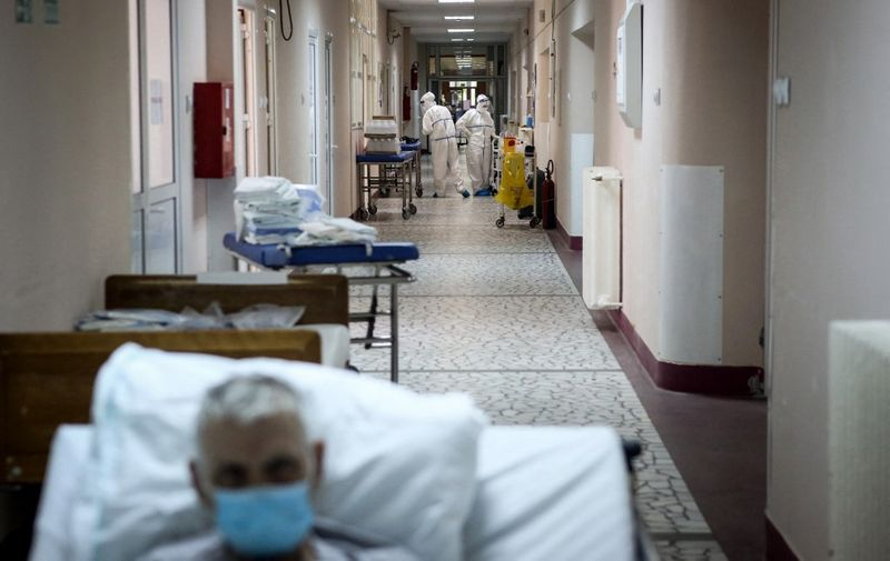 """Medical workers escort a patient suffering from coronavirus disease (COVID-19) inside the Institute for Orthopaedic Surgery """"Banjica"""", recently transformed to a COVID hospital, in Belgrade on July 14, 2020. - A candidate for the European Union, this small Balkan country is experiencing a resurgence of the pandemic, which has sparked several evenings of violent demonstrations to denounce the government's management of the health crisis. With 300 new cases now detected every day, Serbia is approaching April levels, at the peak of the first wave. (Photo by Oliver BUNIC / AFP)"""